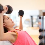 woman at the gym strength training by lifting dumbbells