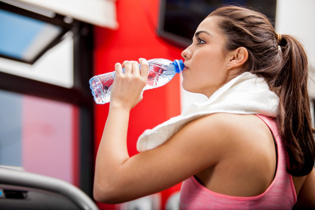 woman drinking water before her workout