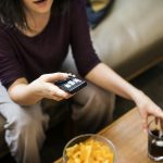 woman overindulges on snack food as she watches TV