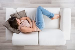 women taking a short nap on her couch to improve weight loss