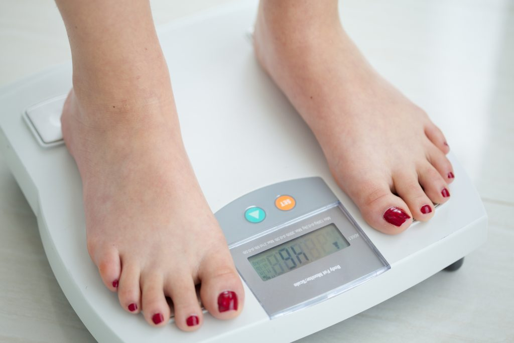 a picture of a woman's feet standing on a body fat percentage scale