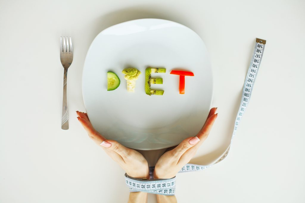 A conceptual image of a small amount of food on a plate that spells out diet. A woman's hands are near the plate bound with a measuring tape.