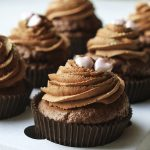 chocolate cupcakes with icing and heart-shaped sprinkles