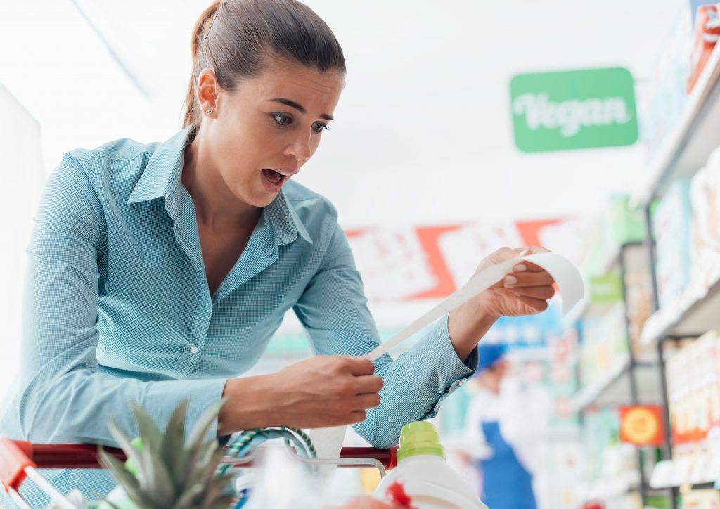 Woman checking the grocery receipt at the supermarket, she is shocked and gasping because the bill is very expensive