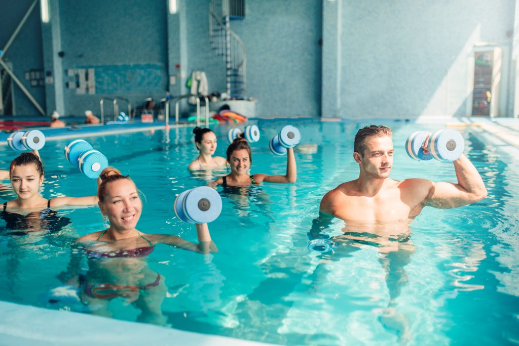 a group of young adults performing aerobic exercises in the pool to stimulate brain function