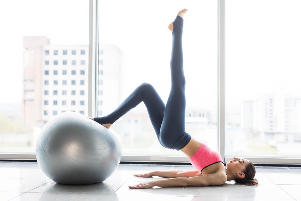woman doing Pilates exercises to strengthen core and for improving back pain