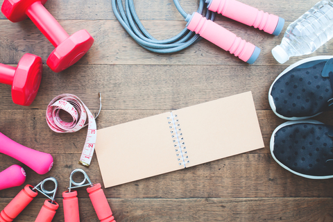 Fitness and weight loss concept, dumbbells, jump rope and measuring-tape on wooden background.