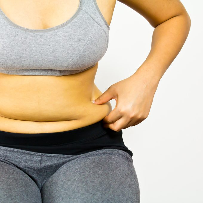 woman pinching stomach fat